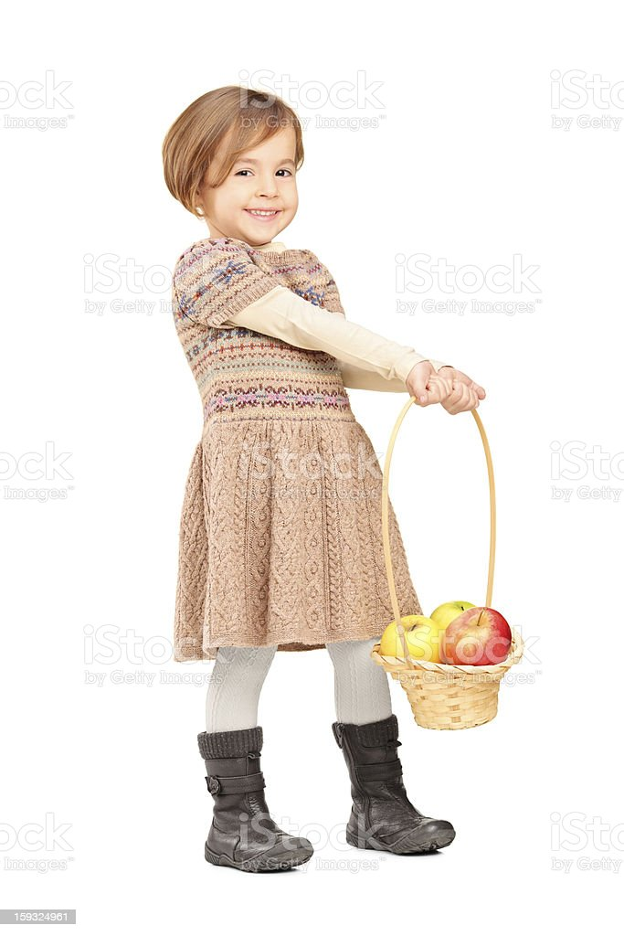 Cute little girl holding a basket with apples royalty-free stock photo