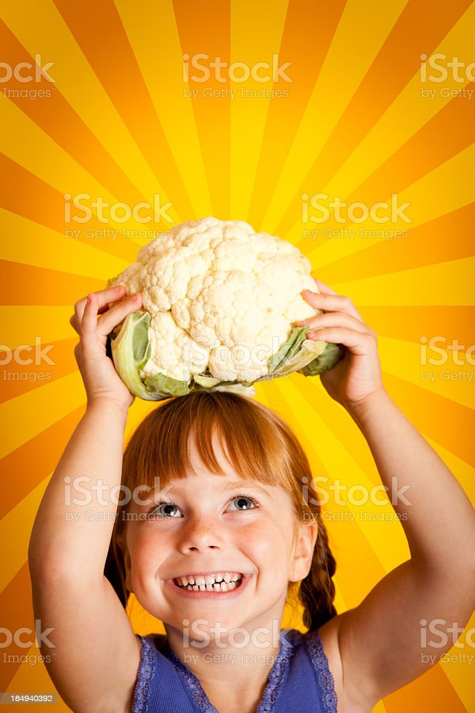 Cute Little Girl Holding Cauliflower Over Her Head and Smiling royalty-free stock photo