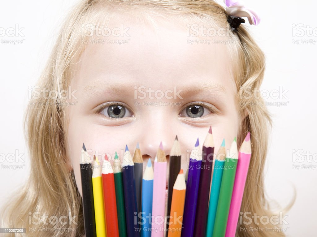 Cute Little Girl Holding Crayons And Looking Above Them royalty-free stock photo