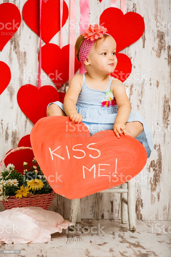 Cute little girl holding Kiss me message stock photo
