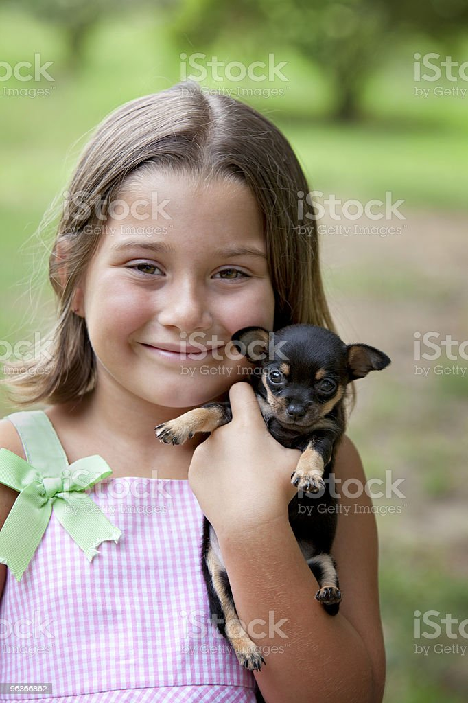 Cute little girl holding tiny puppy royalty-free stock photo