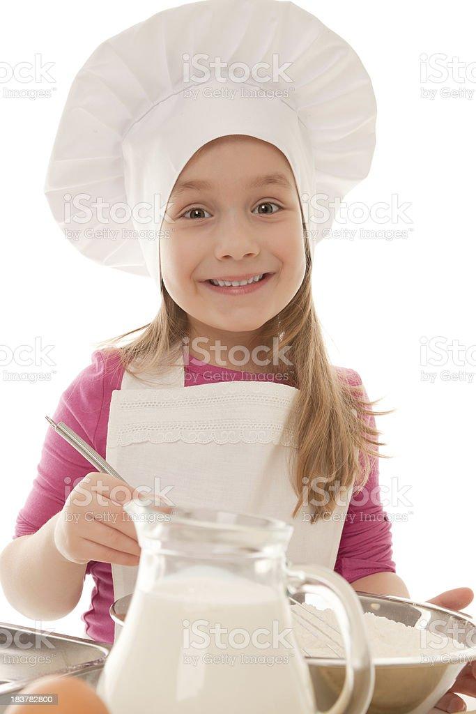 Cute little girl in baker's uniform preparing pastry royalty-free stock photo