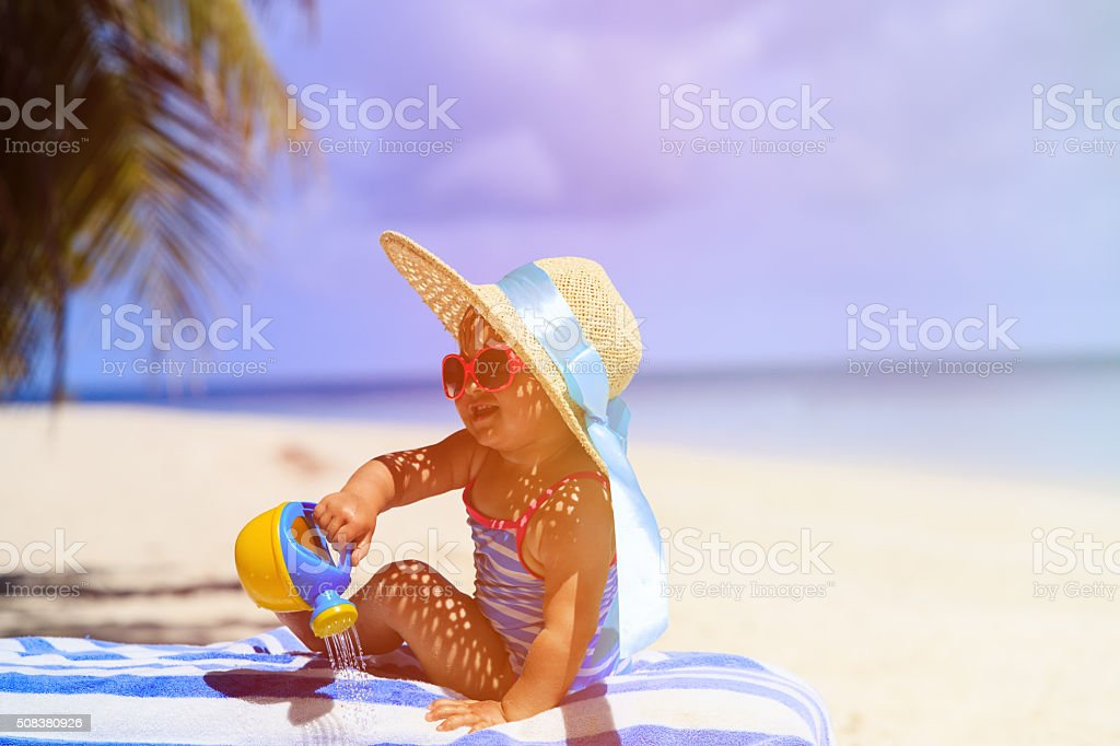 cute little girl in big hat on tropical beach stock photo