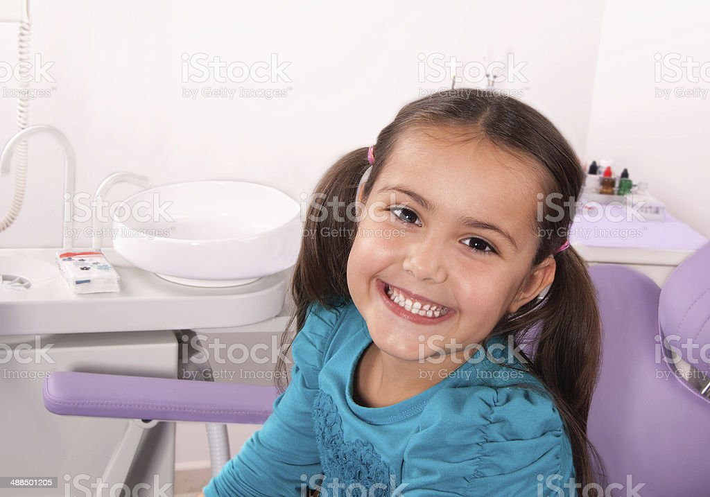 cute little girl in dental chair smiling stock photo