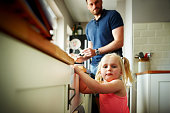 Cute little girl in kitchen with her father in background