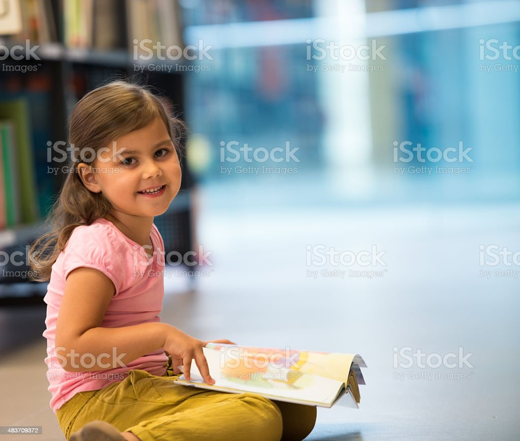 Cute Little Girl In Library stock photo