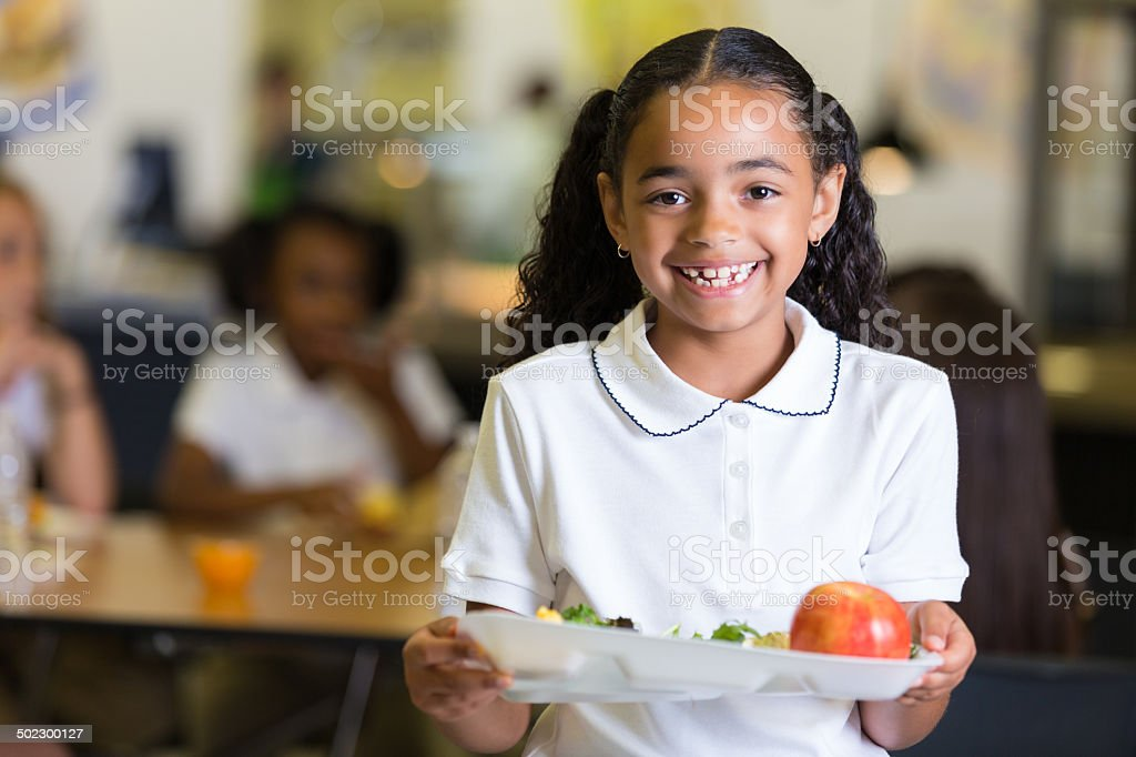 Cute little girl in school cafeteria with food tray stock photo