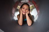 Cute little girl inside of an outdoor play equipment.