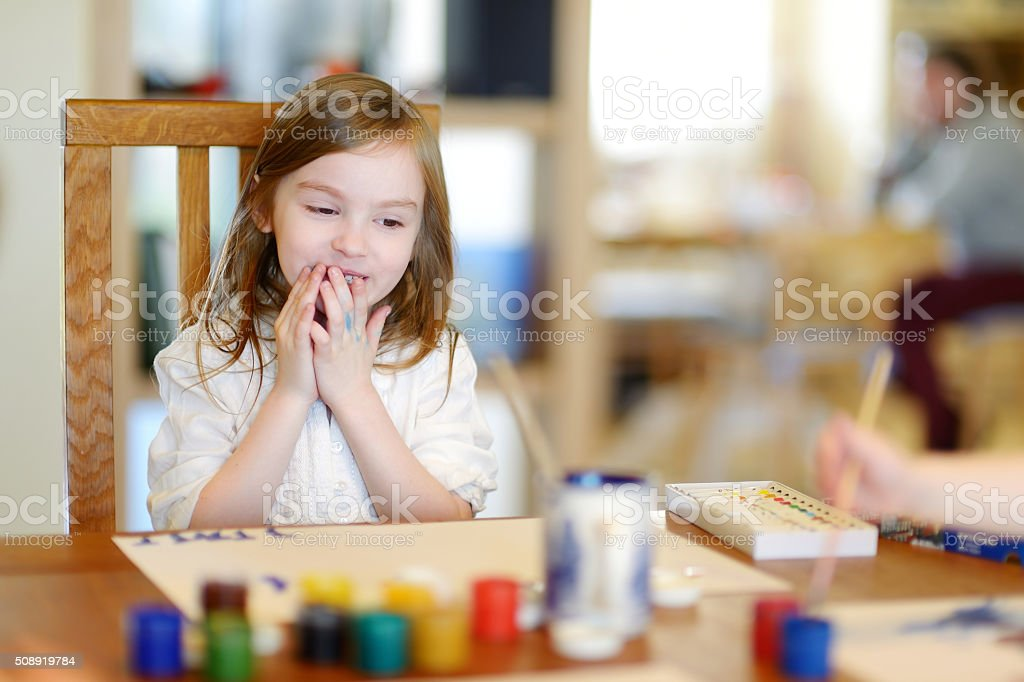 Cute little girl is drawing with paints stock photo