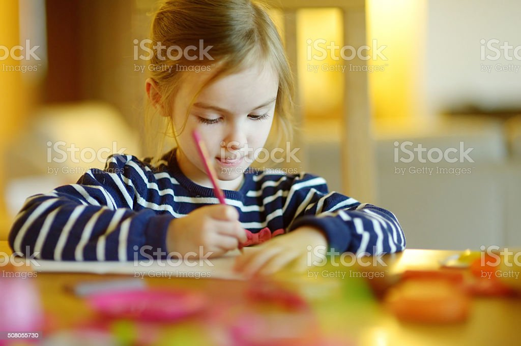 Cute little girl is drawing with pencils stock photo