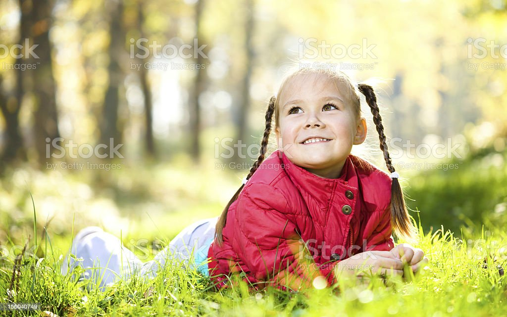 Cute little girl is playing with leaves in park royalty-free stock photo