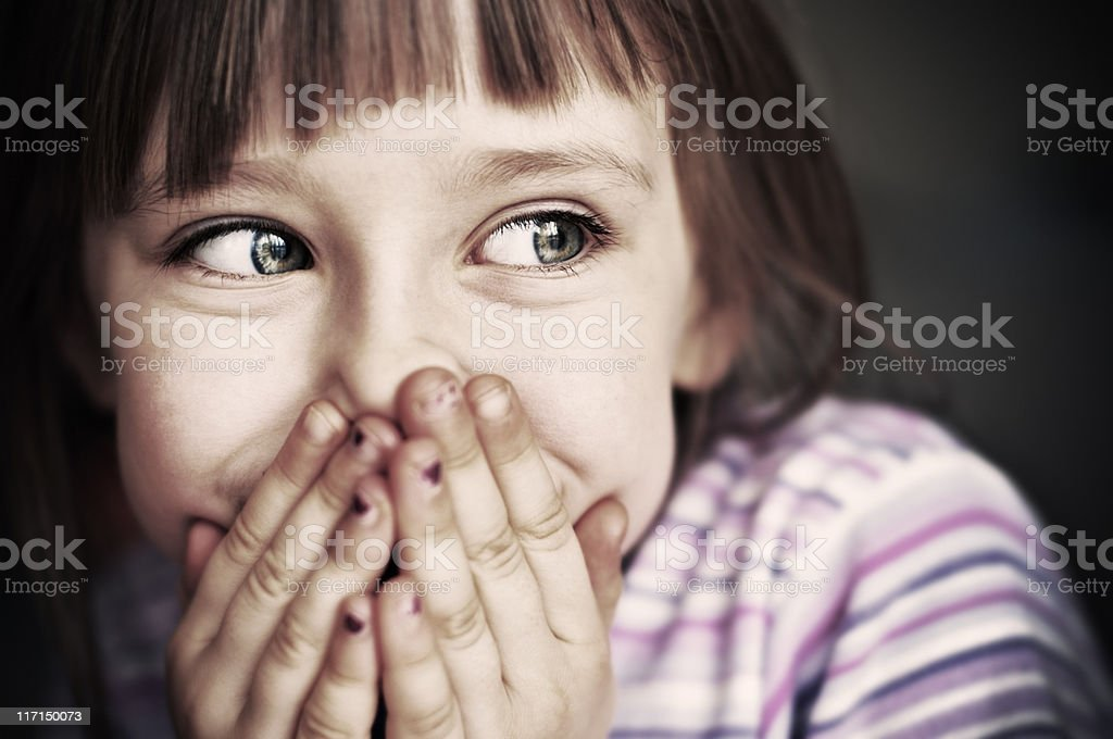 Cute little girl laughing and covering mouth royalty-free stock photo