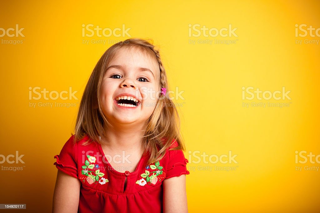 Cute Little Girl Laughing While on Yellow Background stock photo