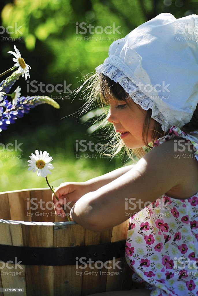 Cute little girl looking on her flower royalty-free stock photo