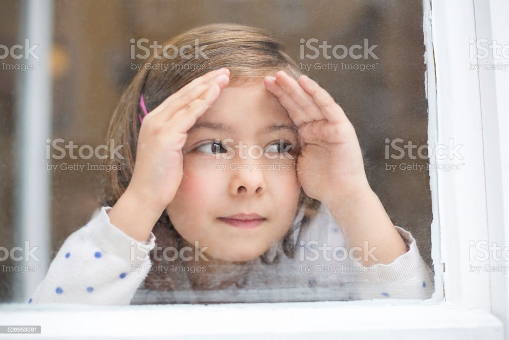Cute little girl looking outside window stock photo