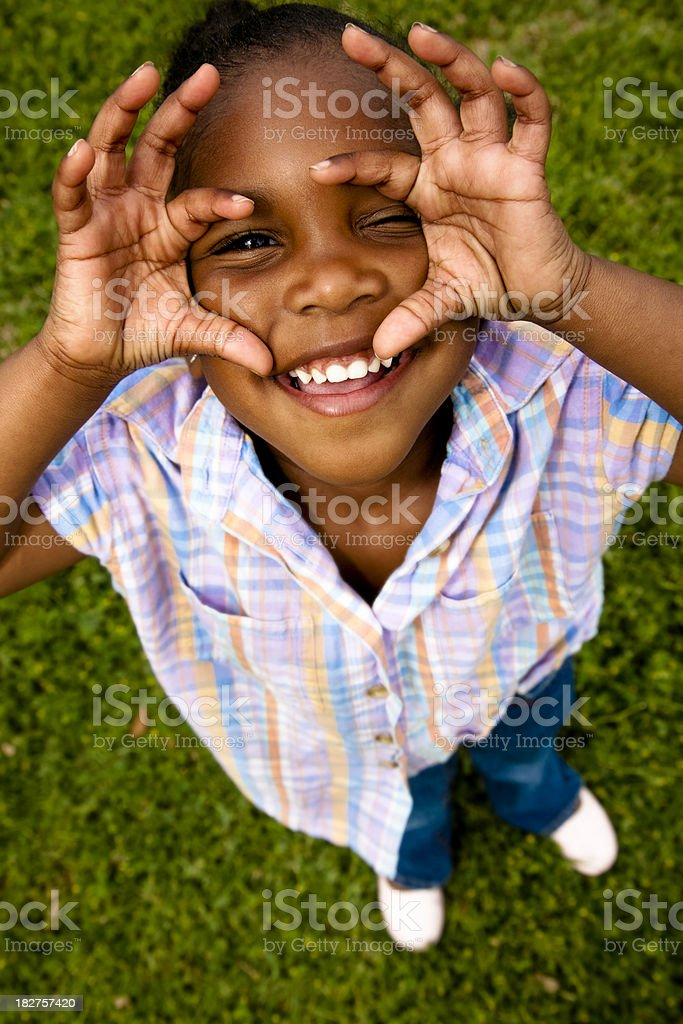 Cute little girl looking through hands like using a camera royalty-free stock photo