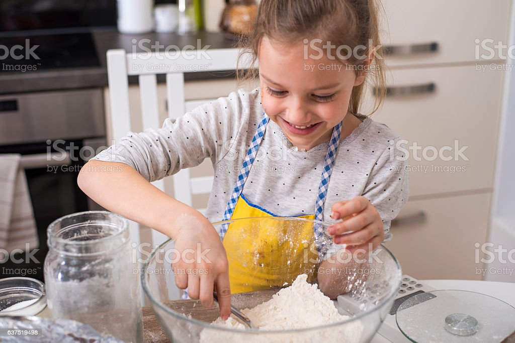 Cute little girl making muffins stock photo