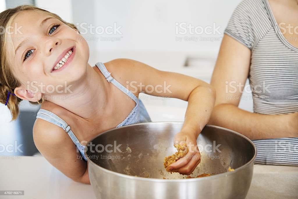 Cute little girl mixing cookie dough with hand. royalty-free stock photo