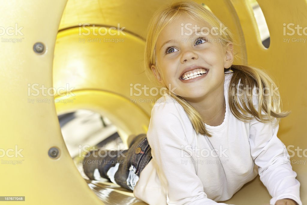 Cute Little Girl on a Playground Slide stock photo