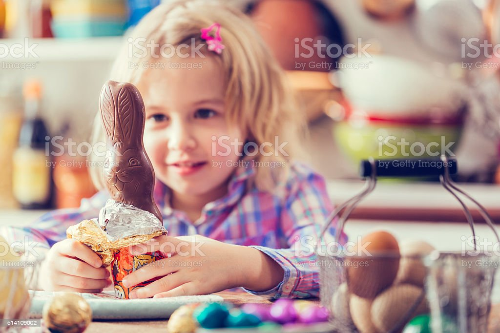 Cute Little Girl Opening Chocolate Easter Bunny stock photo