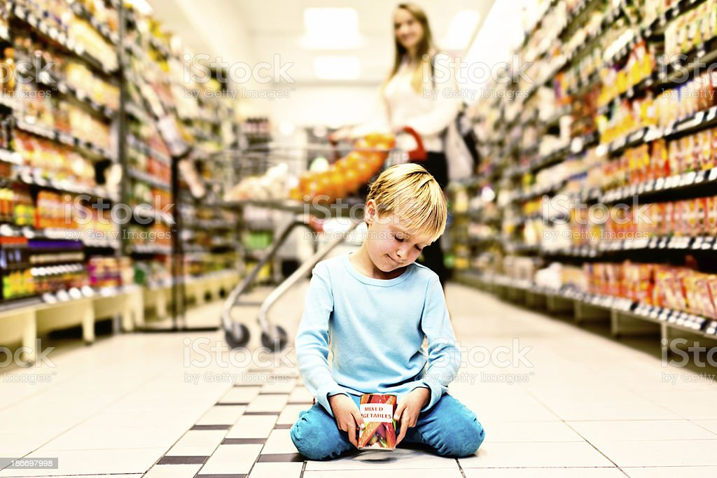 Cute little girl picks up dropped can in supermarket stock photo