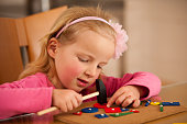 Cute little girl pin pointing blocks into wooden board playing