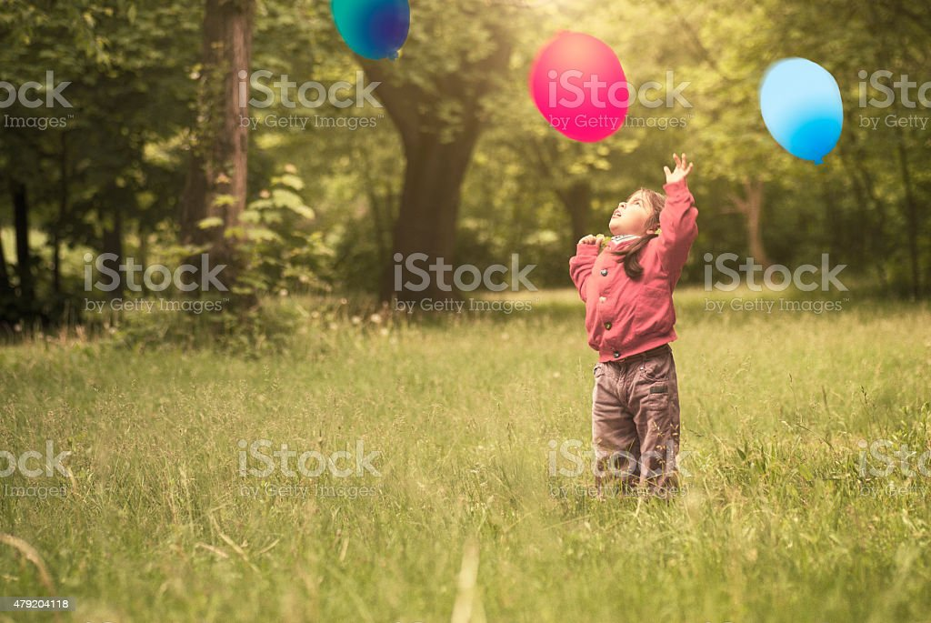 Cute little girl playing alone in park stock photo