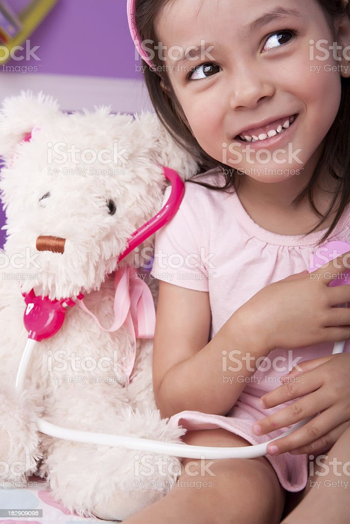 Cute little girl playing doctor to teddy bear royalty-free stock photo