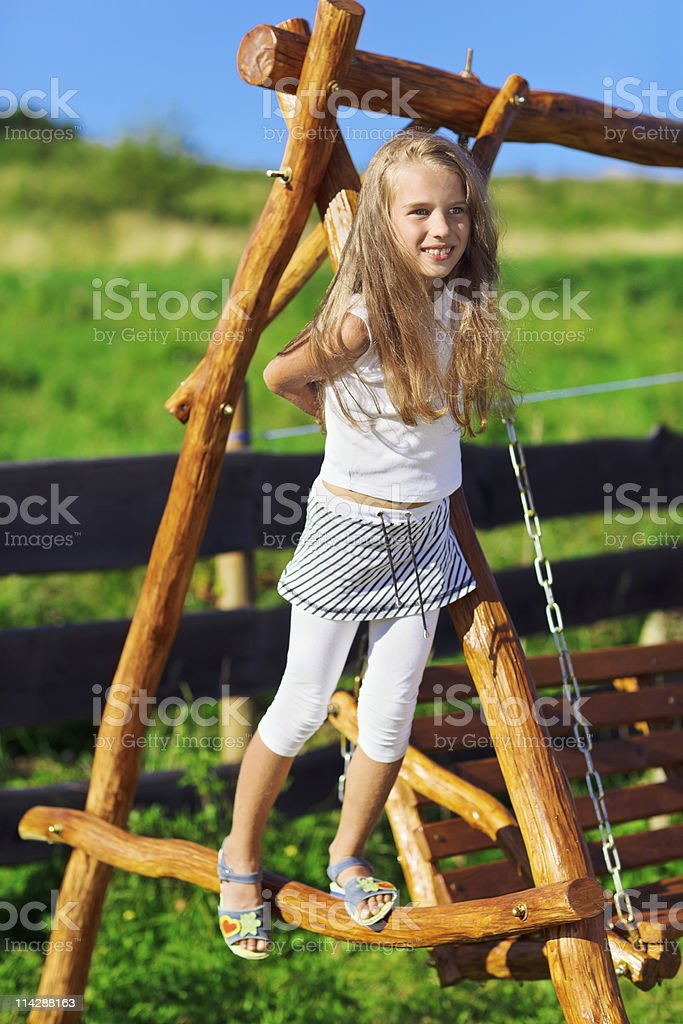 Cute little girl playing on wooden chain swing stock photo