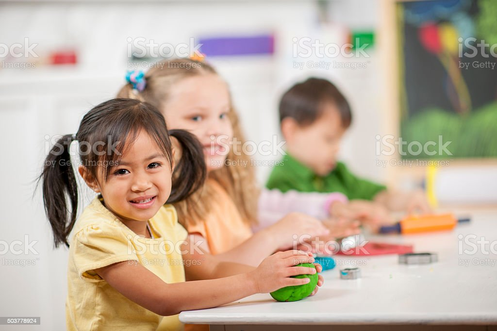 Cute Little Girl Playing with Clay stock photo