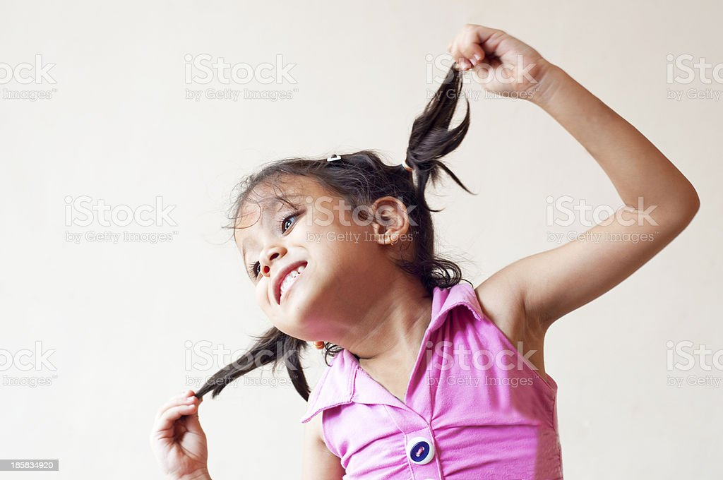 Cute little girl playing with her hair royalty-free stock photo