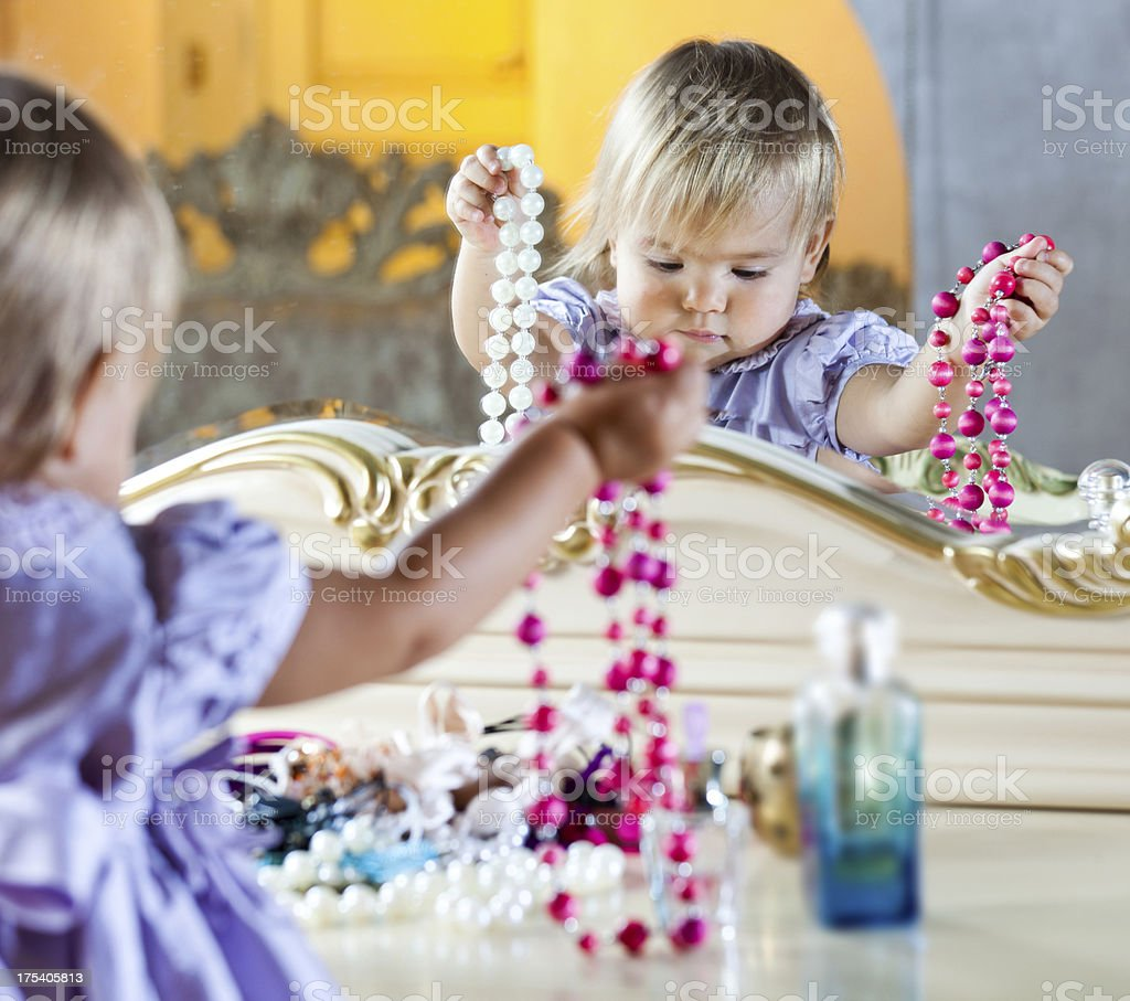 Cute little girl playing with mother's jewelry stock photo