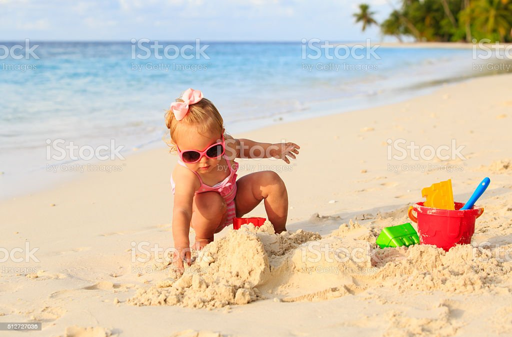 cute little girl playing with sand on beach stock photo