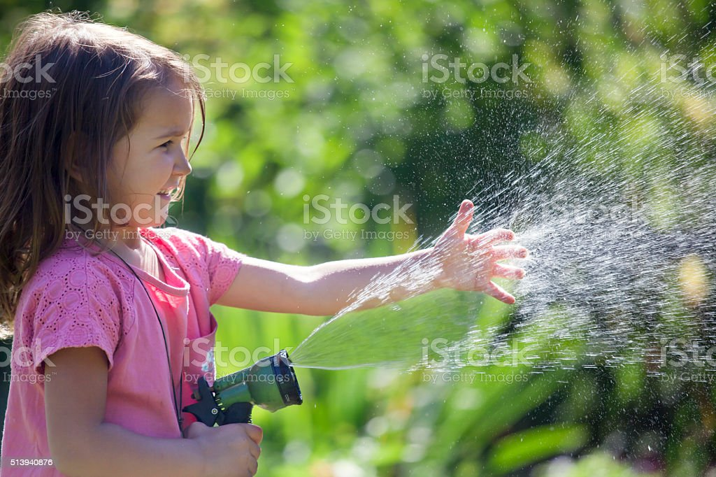 Cute little girl playing with water in the garden stock photo