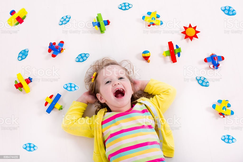 Cute little girl playing with wooden airplane stock photo