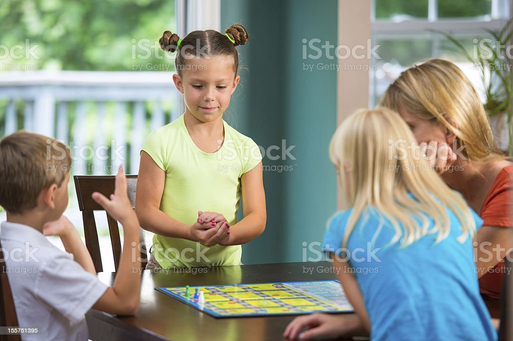 Cute little girl plays board game with family stock photo