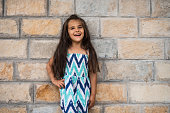 Cute little girl posing against the wall.