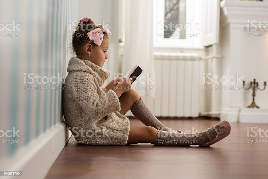 Cute little girl reading a book on floor. stock photo