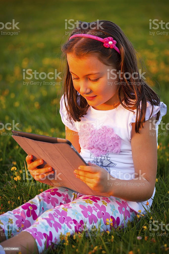 Cute Little girl reading on tablet royalty-free stock photo