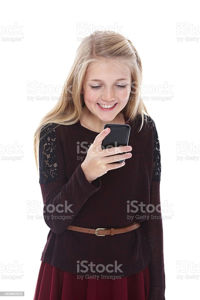 Cute little girl reading  text message on cell phone smiling royalty-free stock photo