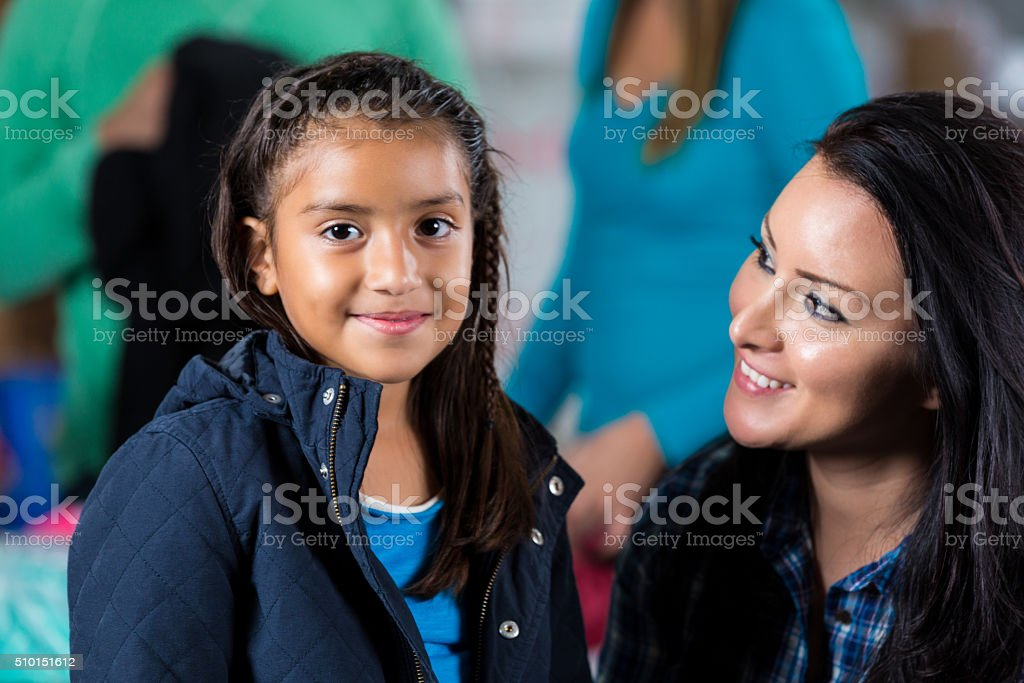 Cute little girl receives warm jacket at community clothing drive stock photo