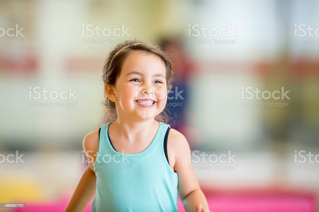 Cute Little Girl Running in the Gym stock photo