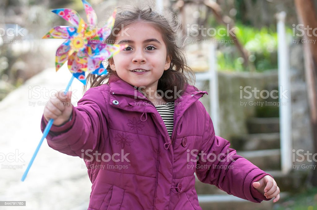 Cute little girl running with pinwheel stock photo