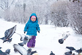Cute little girl scared pigeons
