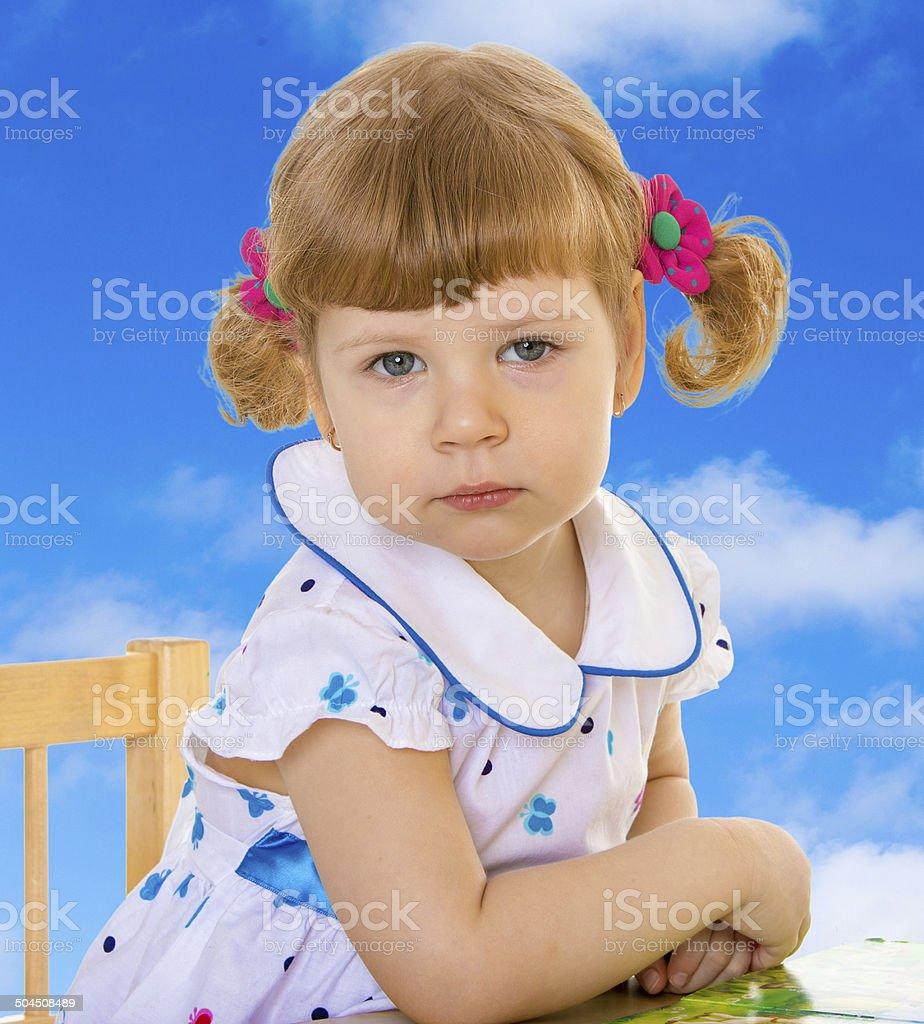 Adorable petite fille assise à la table. photo libre de droits