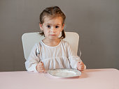 Cute little girl sitting on table with plate, holding fork