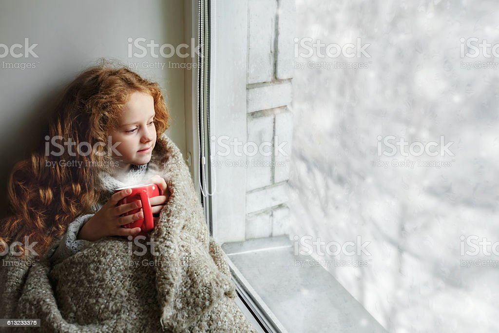 Cute little girl sitting with a cup by the window stock photo