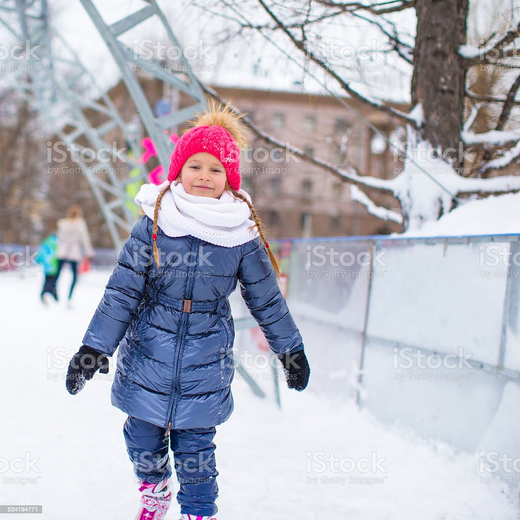 Cute little girl skating on the ice rink outdoors stock photo
