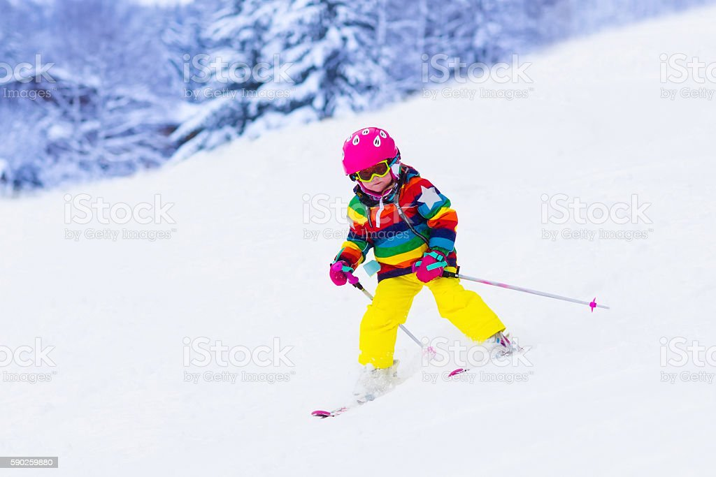 Cute little girl skiing in the mountains stock photo