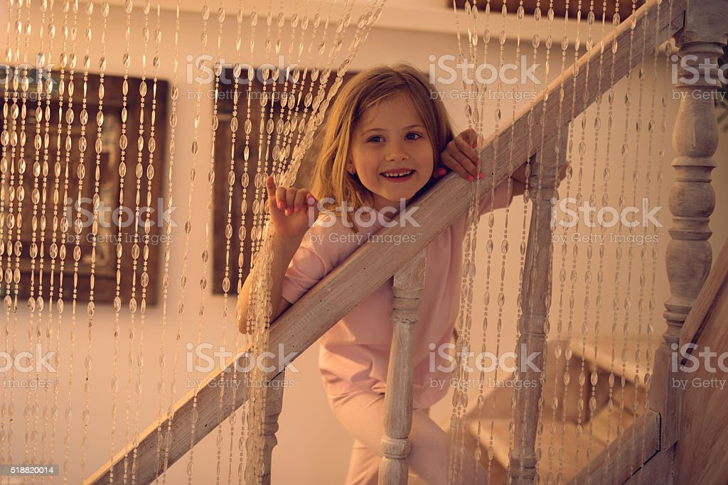 Cute little girl standing on staircase at home. stock photo